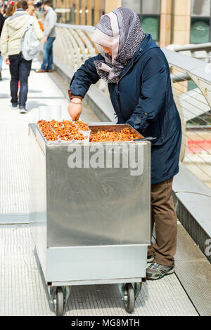 London, United Kingdom - May 2, 2015: Street vendor selling sweet roasted nuts on the Millennium Bridge fills containers ready for sale. - Stock Photo