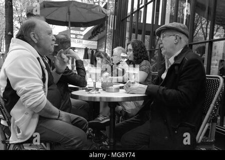 Two elderly French gentlemen talking over a drink at a street cafe on the Avenue de Suffren, near the Eiffel Tower, Paris - Stock Photo