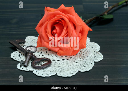A beautiful orange rose resting on an antique doilie, next to vintage keys.  Macro. - Stock Photo