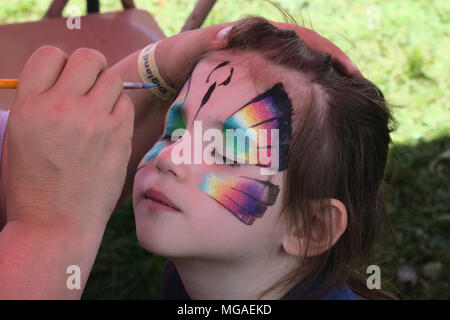 Four-year-old girl having her face painted with a butterfly and a summertime carnival - Stock Photo