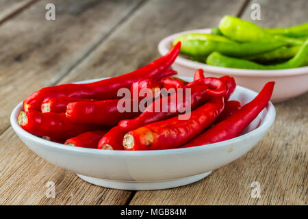 Red hot chili paper in cup on old wooden table - Stock Photo