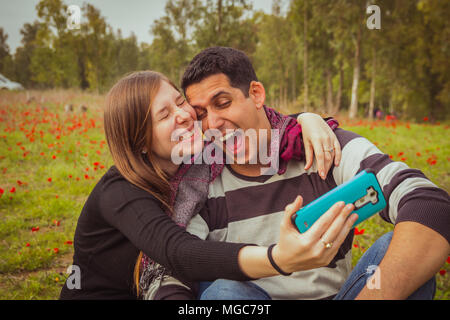 Couple doing silly and funny faces while taking selfie picture with their mobile phone in field of red poppies. - Stock Photo