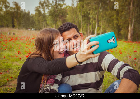 Couple taking selfie picture with their mobile phone in field of red poppies. - Stock Photo
