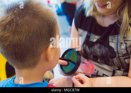 Young boy drinks sweet shaved ice at ice cream parlor - Stock Photo