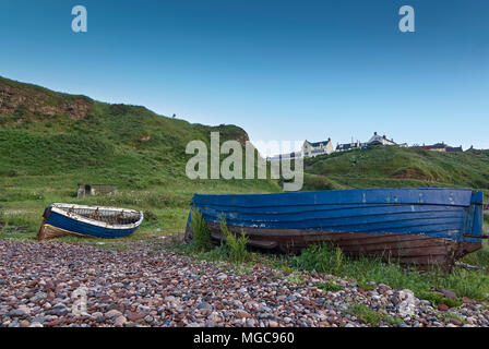 A pair of old abandoned open Wooden fishing Boats lie on the beach below the Cliff top Village of Auchmithie, near Arbroath, in Angus, Scotland. - Stock Photo
