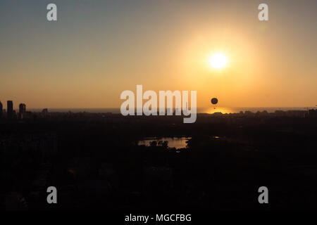 Tel Aviv skyline at sunset - silhouette. Can see a hot air balloon flying in the air. In addition, can see the neighborhood in north Tel Aviv, Hayarko - Stock Photo