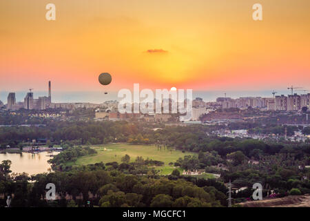 Tel Aviv skyline at sunset. Can see a hot air balloon flying in the air. In addition, can see the neighborhood in north Tel Aviv, Hayarkon Park, Readi - Stock Photo