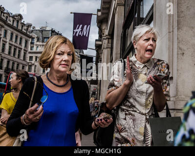 Two women walking along street, in a hurry, with startled expressions, London, England, UK - Stock Photo