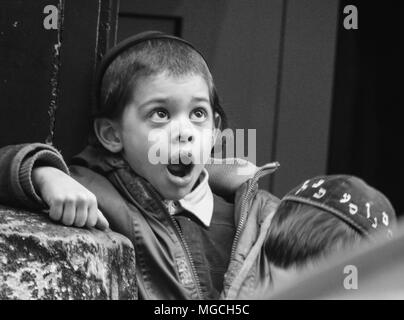 Young Jewish boy wearing kippah, looking up with shocked expression, mouth open, black and white, New York City, USA - Stock Photo