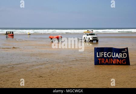 Perranporth, Cornwall, UK - April 9 2018: RNLI lifeguards training in surf on a beach, with truck, dinghies and jetskis, behind a large sign. - Stock Photo