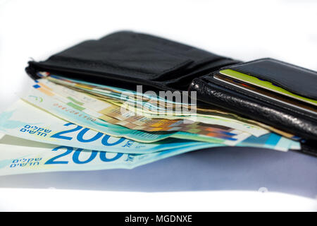 Stack of various of israeli shekel money bills in open black leather wallet. - Stock Photo