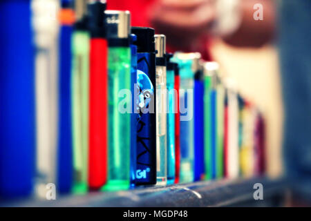 Lighters lined up. One lighter blue color stands out from the rest. Man's face Illustrated on it and it looks like he glances out. Narrow focus. - Stock Photo