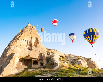 Colorful hot air balloons flying over rock landscape at Cappadocia Turkey - Stock Photo