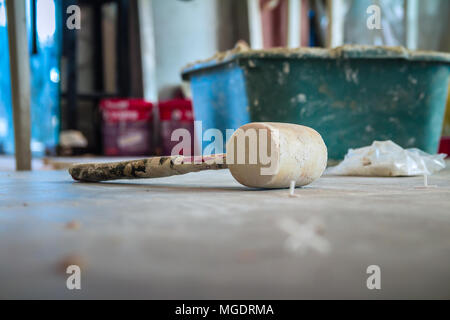 Wooden hammer on the floor in construction site. - Stock Photo
