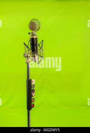 Vocal condenser microphone with wind screen isolated on green background. - Stock Photo