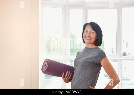 Mature woman holding rolled up exercise mat at gym. Cheerful female fitness instructor holding mat - Stock Photo