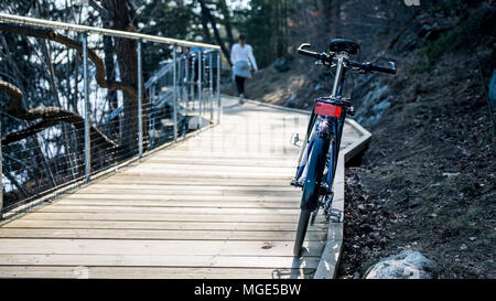 Hybrid sport street city bike on wooden pathway near water and rocky shore with blurred girl in background - Stock Photo