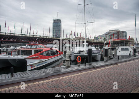 Sydney, NSW, Australia-December 6,2016: Darling Harbour with nautical vessels and the Pyrmont Bridge under an overcast sky in Sydney, Australia - Stock Photo