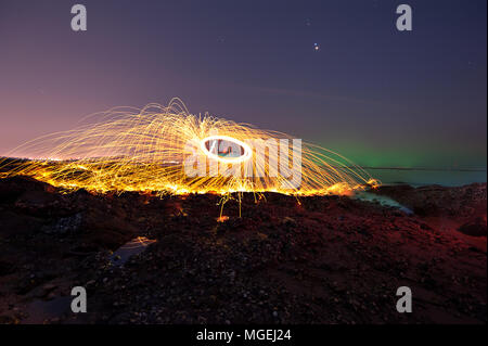 Showers of hot glowing sparks from spinning steel wool on the beach - Stock Photo