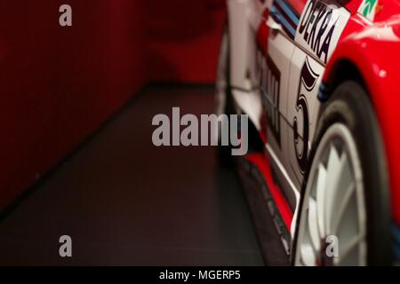 Side by side of a Lancia Delta Integrale, the side of the machine is focused on while the red background is out of focus - Stock Photo