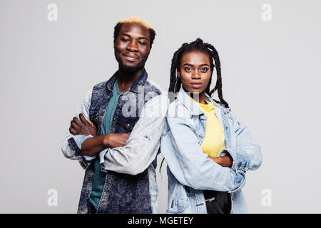 Portrait of an upset young afro american couple standing with arms folded isolated over white background - Stock Photo