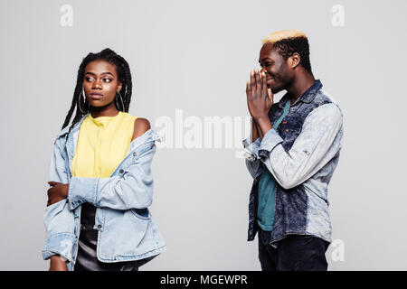 Portrait of an upset young afro american man please his offended young woman isolated over white background - Stock Photo