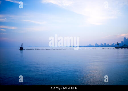 Cool blue minimalist Chicago skyline landscape viewed over Lake Michigan with a pier and navigation beacon in the foreground and silhouetted city on t - Stock Photo