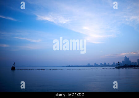 Minimalist blue landscape over Lake Michigan with a breakwater or pier in the foreground and silhouetted Chicago cityscape on the horizon at dusk - Stock Photo