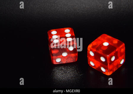 Red luminescent casino gambling dice on black reflecting background - Stock Photo