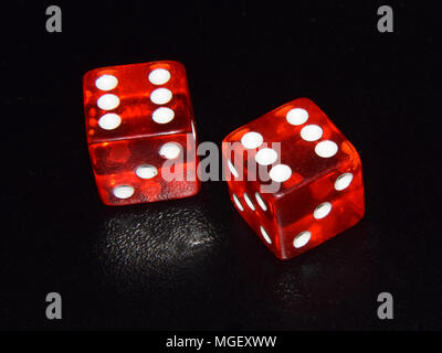 Red luminescent casino gambling dice on black background - double six - Stock Photo