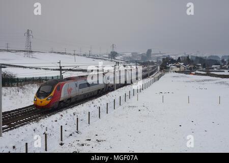 A Virgin trains west coast  Pendolino train passing Shap, Cumbria on the west coast main line  in winter snow - Stock Photo