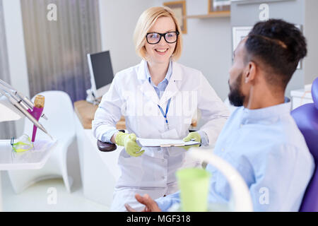 Smiling pretty stomatologist wearing rubber gloves and white coat holding clipboard in hands while asking male patient about his complaints, interior  - Stock Photo