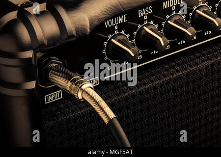 Close up shoot of a black bass guitar amplifier with a jug plugged in - Stock Photo