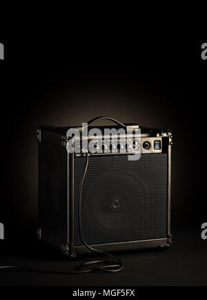 Black bass guitar amplifier whit a cord plugged in on black background - Stock Photo