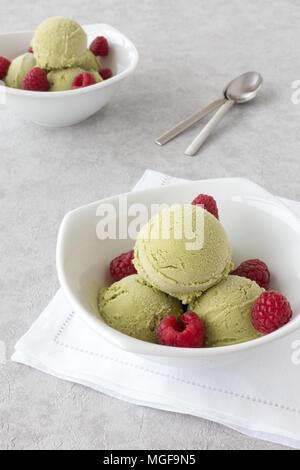 Scoops of homemade organic matcha ice cream and fresh raspberries in two white porcelain bowls on gray textured background. - Stock Photo