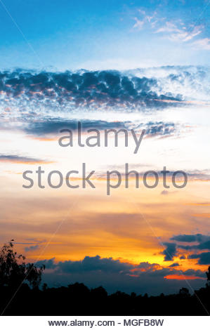 A sunset on a cloudy day in rainy season. See the saturated colors. - Stock Photo
