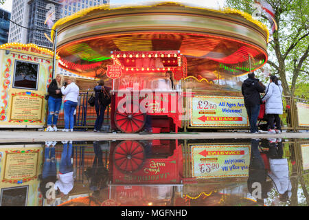 South Bank, London, 28th April 2018. Following a rather cold and wet day across London, puddles form on the South Bank, creating colourful reflections of a nearby merry-go-round. Tourists and Londoners however are undeterred by the weather, strolling along the river and crowding into bars and cafes near the Southbank Centre. Credit: Imageplotter News and Sports/Alamy Live News - Stock Photo