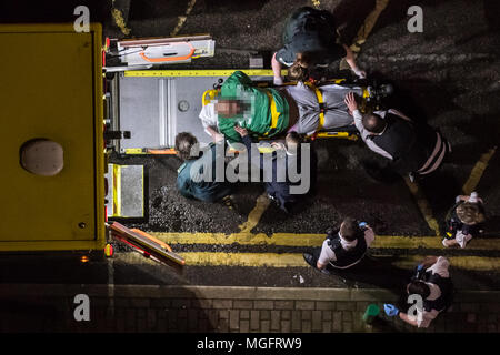 London, UK. 28th April, 2018. A man is forcefully restrained by police and ambulance staff following an incident in Surrey Quays car park. Credit: Guy Corbishley/Alamy Live News - Stock Photo