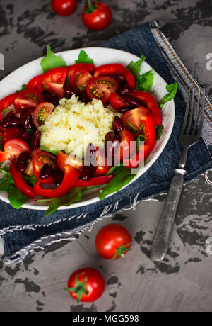 Couscous salad with arugula, cherry tomatoes, pepper and red beans in white plate on dark grey concrete background - Stock Photo