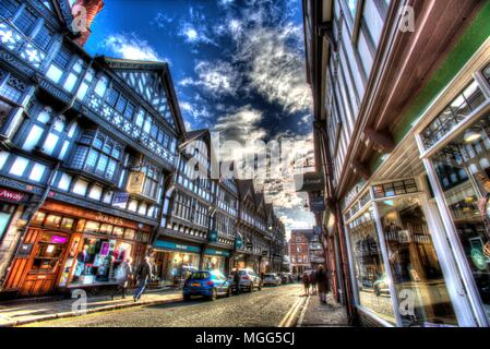 City of Chester, England. Artistic view of shops and pedestrians in Chester's St Werburgh Street. - Stock Photo