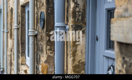 Cast iron water downpipes line up agaist the limestone walls of  terraced cottages in the Cotswold's market town of Chipping Campden - Stock Photo