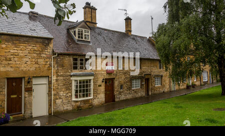 Cotswold limestone adorns the facade of these elegant terraced cottages in the picturesque market town high street of Chipping Campden-one is for sale - Stock Photo