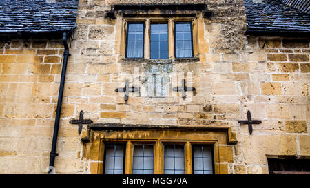 Cotswold limestone is kept in place by four tie plates on the facade of this terraced cottage in the market town high street of Chipping Campden - Stock Photo