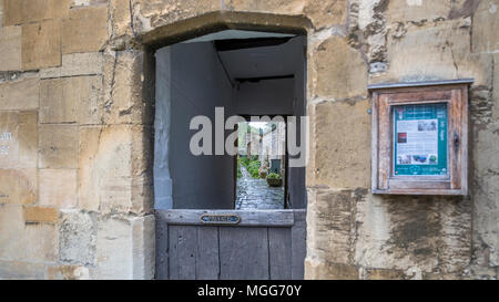 Cotswold limestone surrounds a half doored arched alleyway between terraced houses in the picturesque market town high street of Chipping Campden - Stock Photo