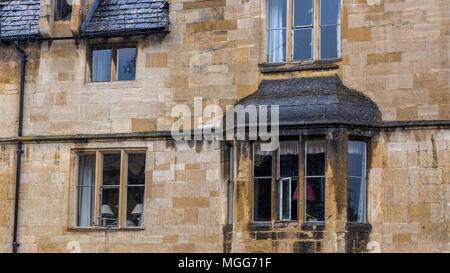 Cotswold limestone adorns the facade and ornate bay of this elegant terraced house in the picturesque market town high street of Chipping Campden - Stock Photo