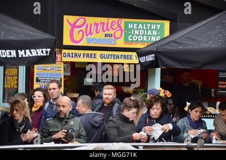 street style food stalls at kerb camden market the stables london UK selling hotdogs fish and chips curries colombian indian and more with tourists - Stock Photo