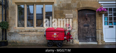 A Royal Mail trolley waits by the Cotswold limestone facade of the terraced Dragon House in the elegant market town high street of Chipping Campden - Stock Photo