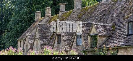 Bibury village's slate roofed row of dormers poke out of their Jacobean architecture - Stock Photo