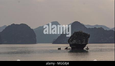 man fishing in small boat among limestone karsts in Ha Long Bay, Vietnam - Stock Photo
