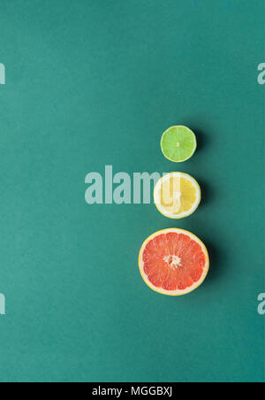 Slices of Cut in Half Organic Citrus Fruits Grapefruit Lemon Lime on Dark Green Background. Imitation of Stop Lights. Superfoods Antioxidants Vitamins - Stock Photo